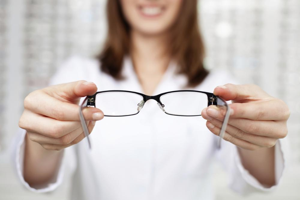 Optometrist passing glasses to client.